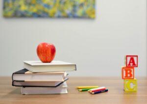 teacher's desk with apple, books, pencils, and ABC blocks