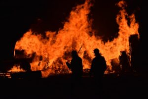 raging fire burning in the night with human figures silhouetted