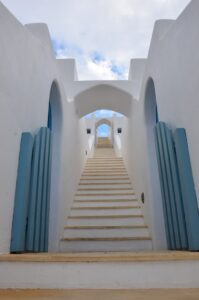 Long stairway with bright white steps toward blue clouds